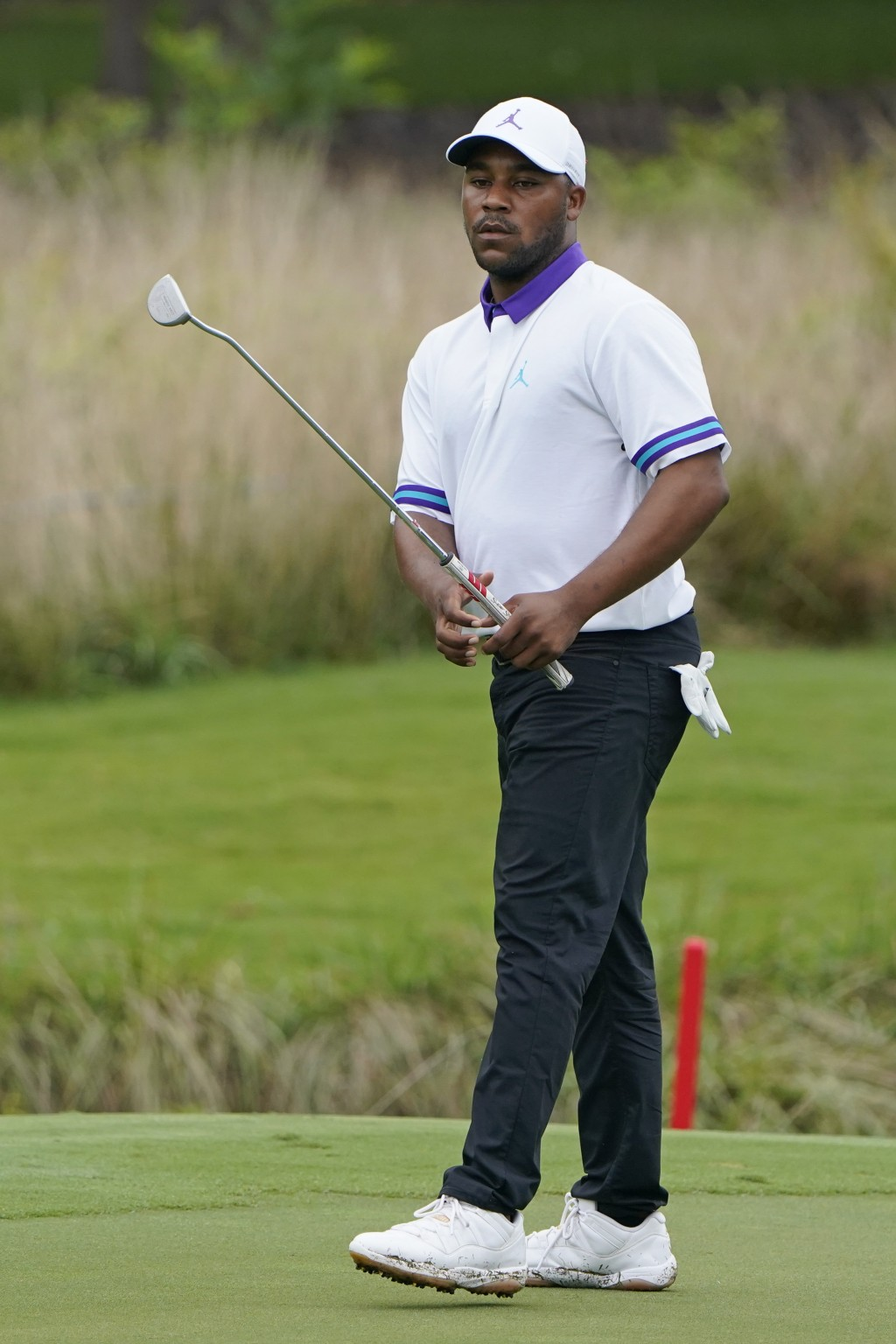 Harold Varner III misses his birdie putt attempt on the seventh hole during the first round of the Wyndham Championship golf tournament at Sedgefield ...