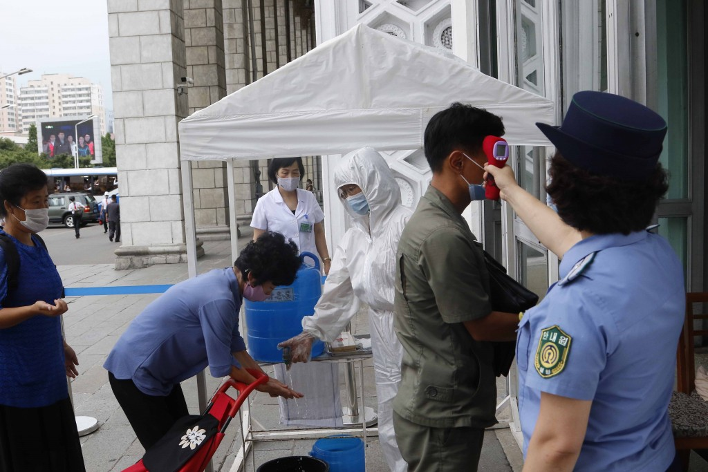 People are disinfected their hands and get fever checked before going into the Pyongyang Railway Station in Pyongyang, North Korea, Thursday, Aug. 13,...