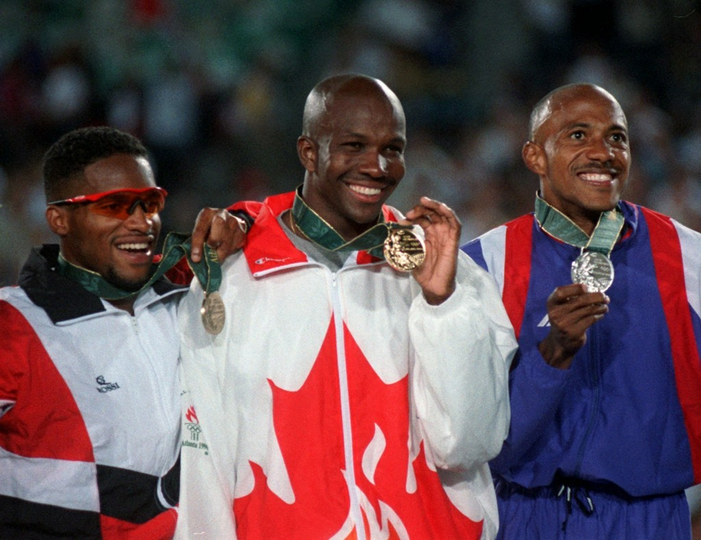 FILE - In this July 27, 1996, file photo, Bronze medalist Ato Boldon of Trinidad and Tobago, left, gold medalist Donovan Bailey of Canada, center, and...