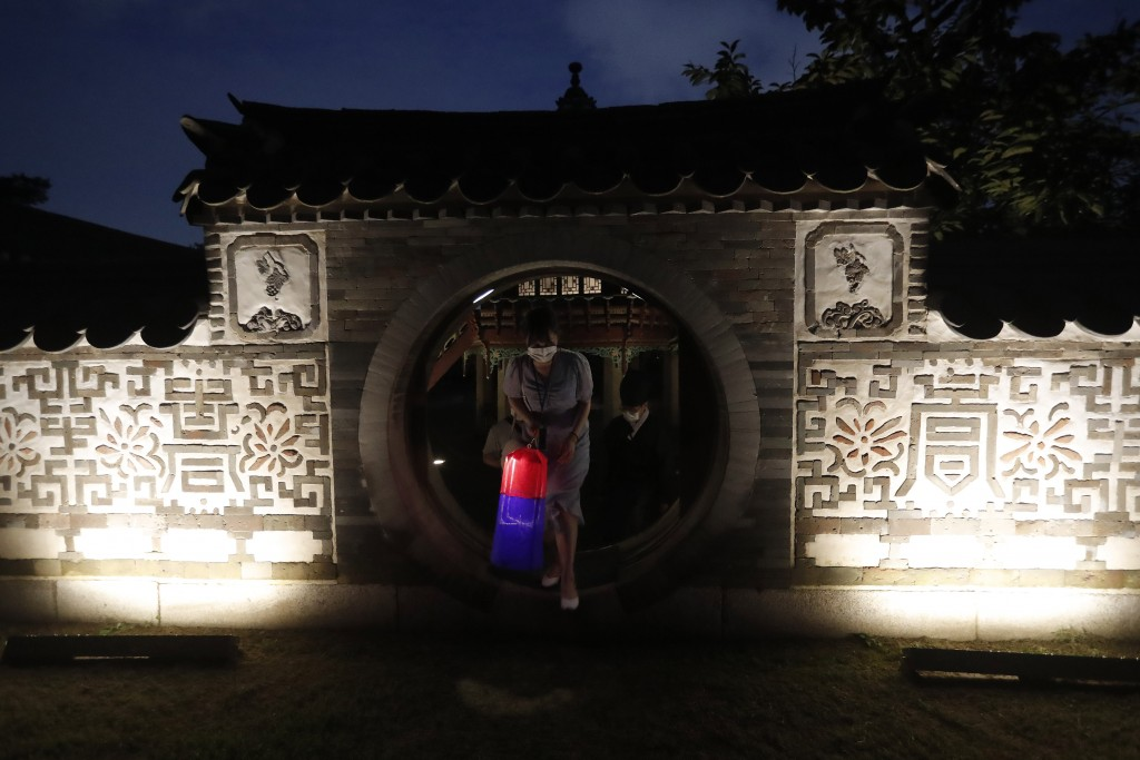 A visitor holding a Korean traditional lantern walks around during the Moonlight Tour at Changdeokgung Palace in Seoul, South Korea, Thursday, Aug. 13...