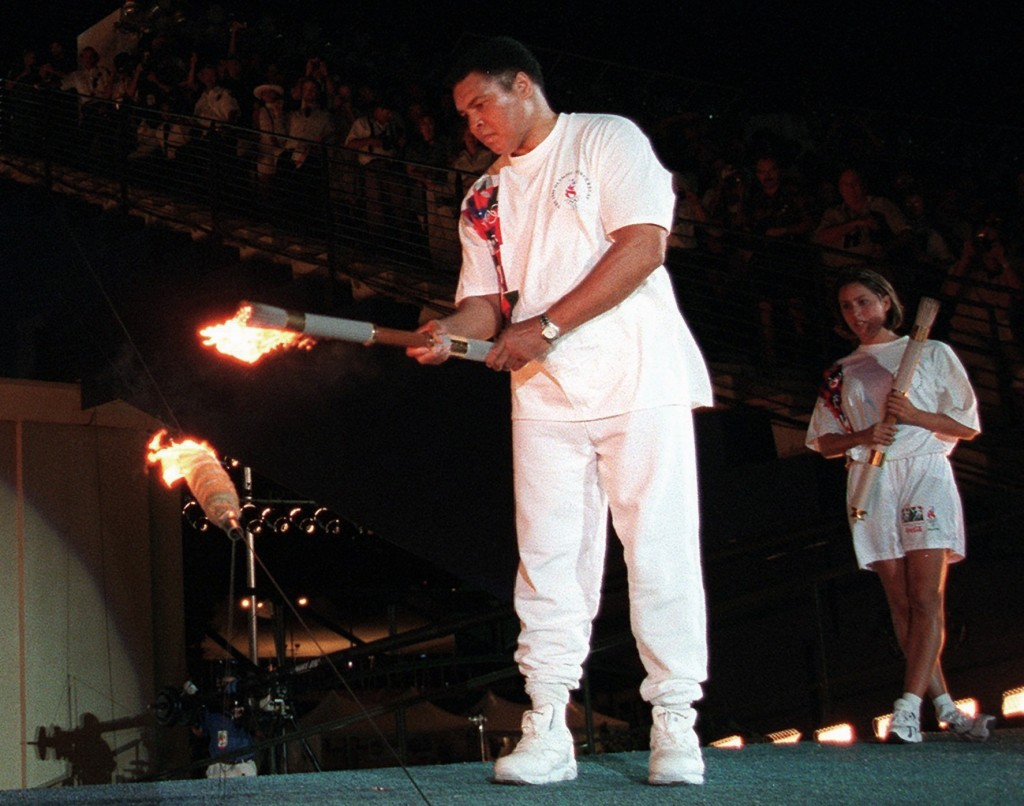 FILE - In this July 19, 1996, file photo, American swimmer Janet Evans , right, looks on as Muhammad Ali lights the Olympic flame during the 1996 Summ...