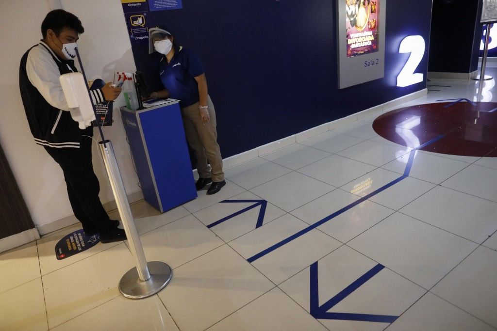 A moviegoer ask a question of an employee at the entrance to the theater halls, marked with tape indications to guide traffic flow, at the Cinepolis m...