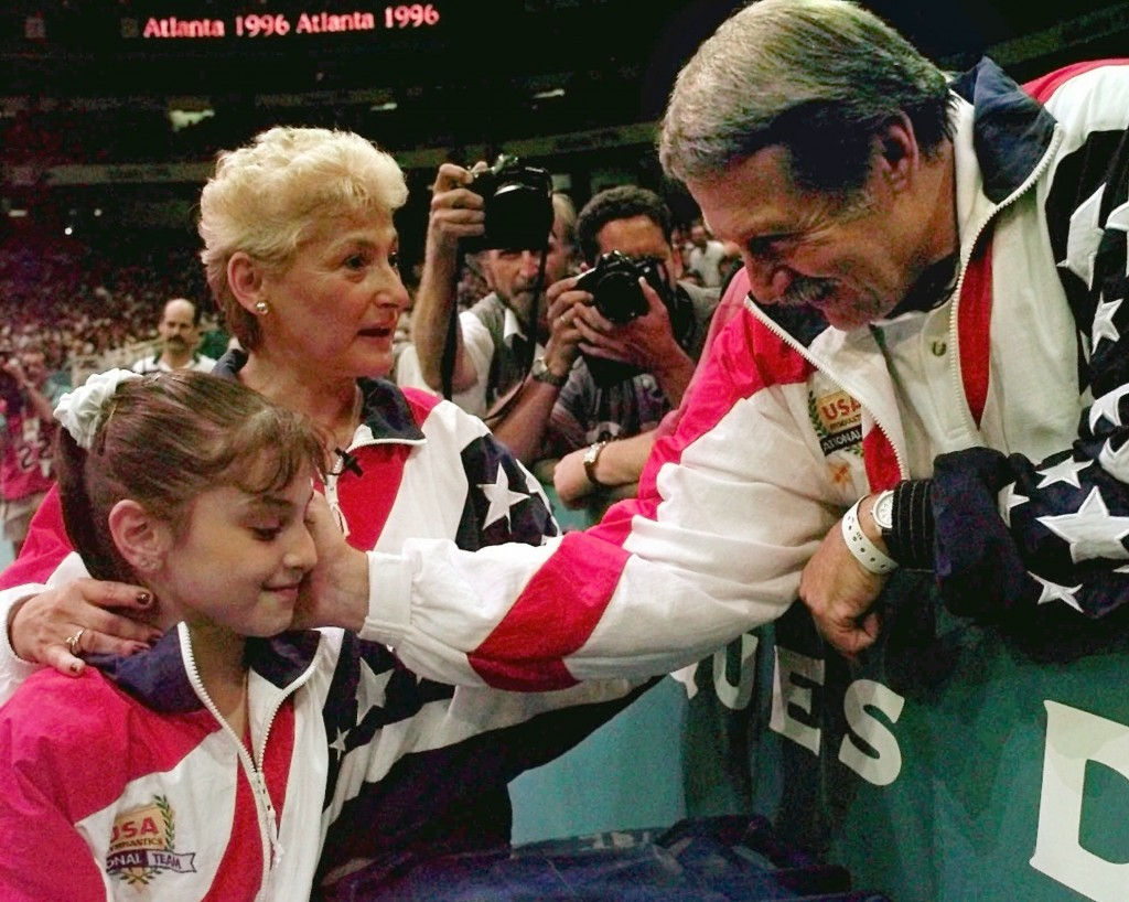 FILE - In this July 23, 1996, file photo, Bela Karolyi, right, congratulates Dominique Moceanu, left, after the United States captured the gold medal ...