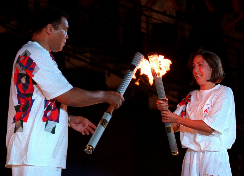 FILE - In this July 19, 1996, file photo, American swimmer Janet Evans passes the Olympic flame to Muhammad Ali during the 1996 Summer Olympic Games O...