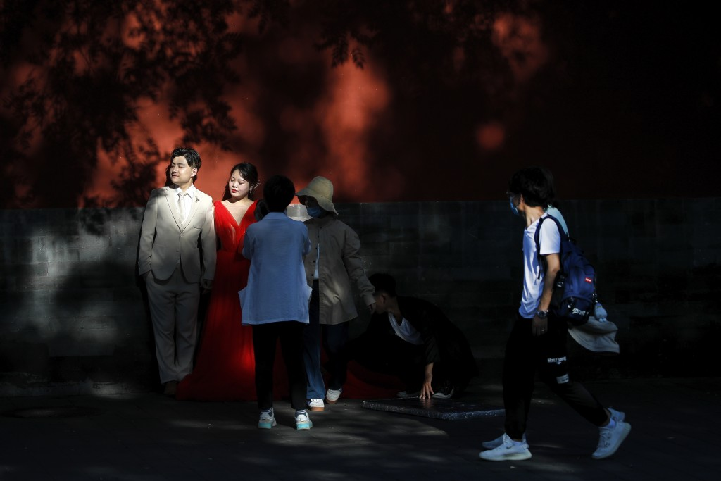 People wearing face masks to help protect against the coronavirus walk by a newly weds posing for wedding photos near the Forbidden City in Beijing, T...