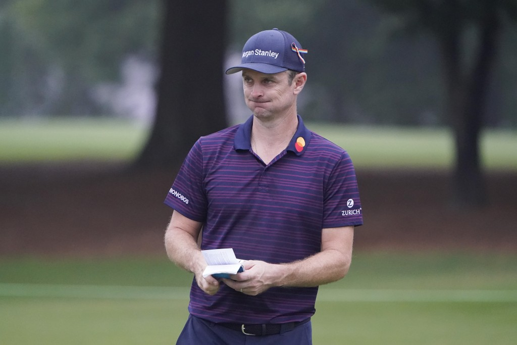 Justin Rose, of England, holds his scorecard on the 10th green after making a bogey during the first round of the Wyndham Championship golf tournament...