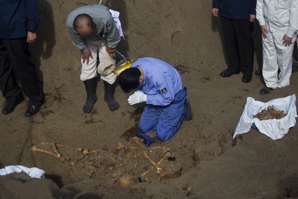 FILE - In this Dec. 14, 2010, file photo, then Japanese Prime Minister Naoto Kan bows at a mass grave site on Iwo Jima island where officials discover...