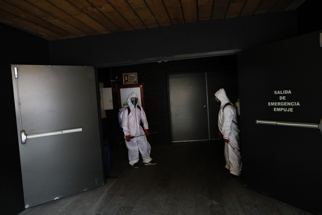 Workers wait for the end of a film to disinfect a theater after a movie screening, at the Cineteca Nacional, Mexico's film archive, in Mexico City, We...