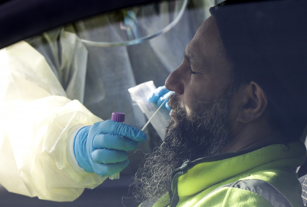 Medical staff take a COVID-19 test from a visitor to a drive through community based assessment centre in Christchurch, New Zealand, Thursday, Aug. 13...
