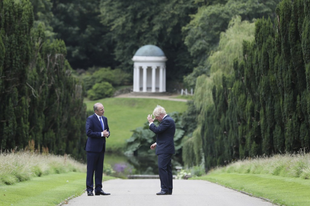 Britain's Prime Minister Boris Johnson, right, and Prime Minster of Ireland Michael Martin walk in the gardens  at Hillsborough Castle during his visi...