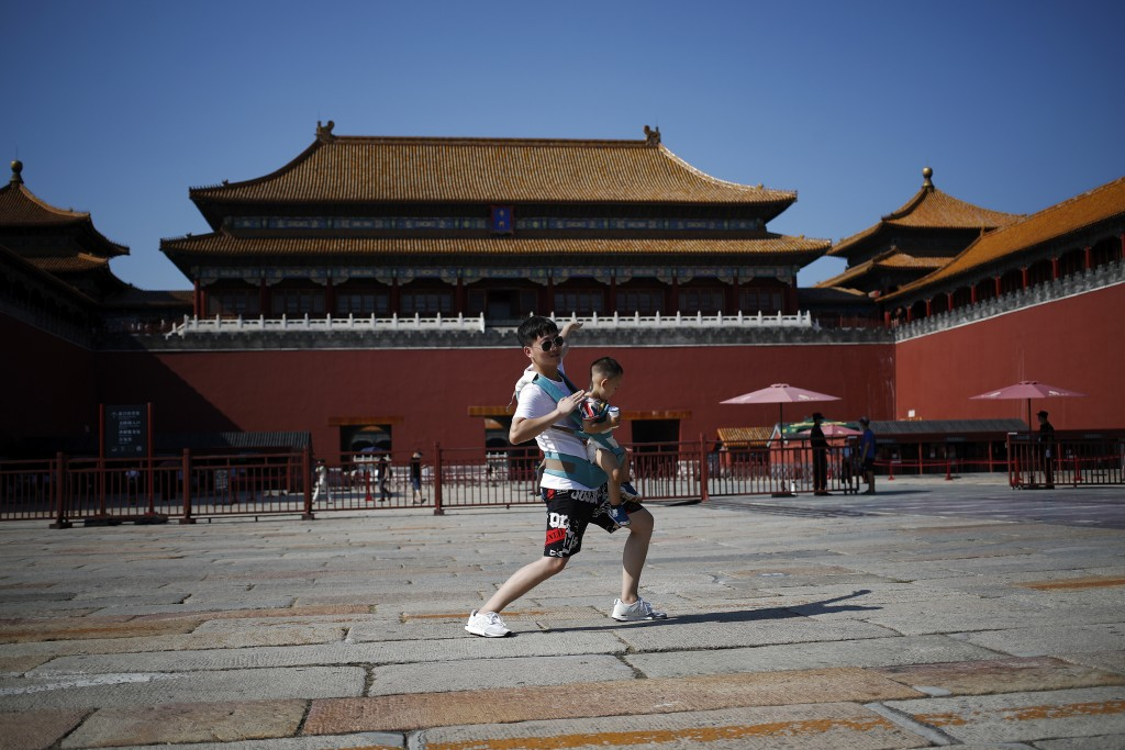 A man carries a child poses in front of the Forbidden City in Beijing, Thursday, Aug. 13, 2020. New local cases in China fell into the single digits, ...