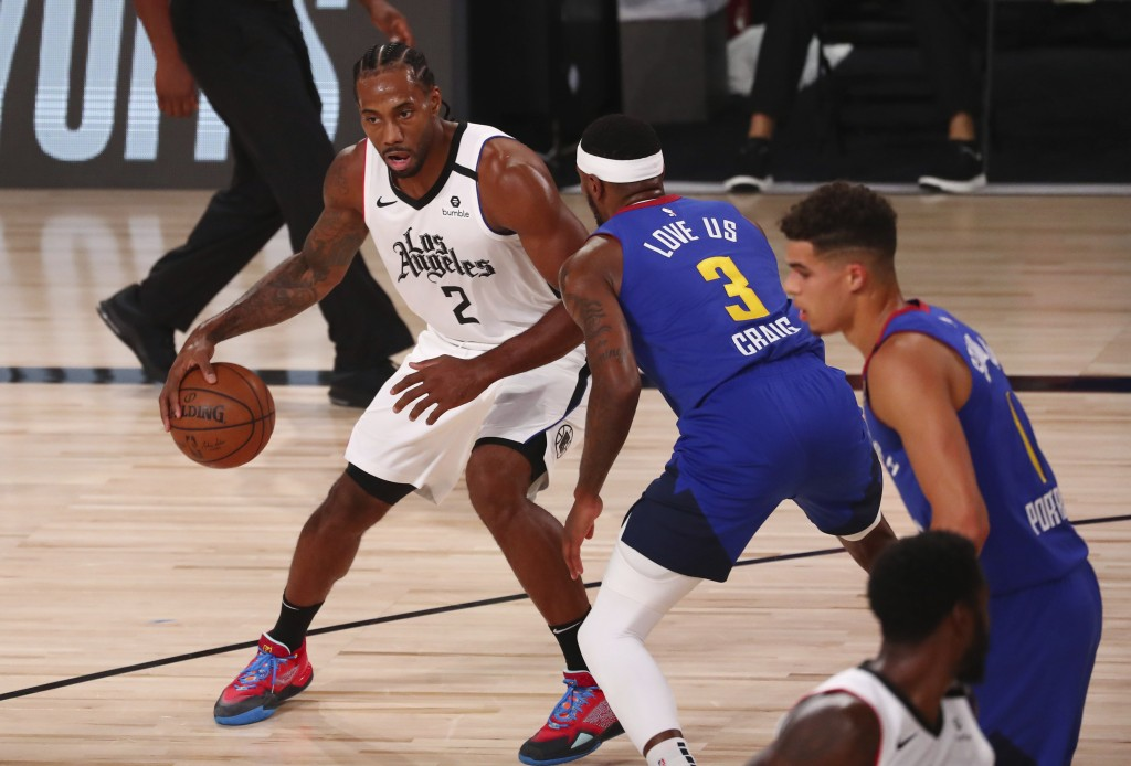Los Angeles Clippers forward Kawhi Leonard (2) drives to the basket against Denver Nuggets forward Torrey Craig (3) in the first half of an NBA basket...