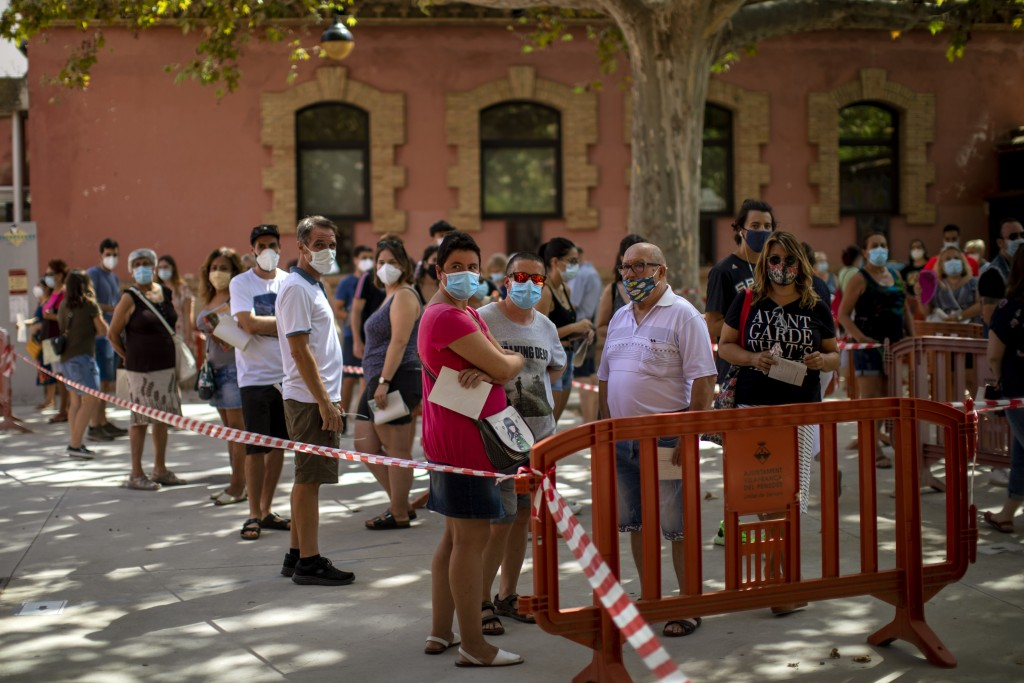 People wearing face masks queue up to be tested for COVID-19, at Vilafranca del Penedes in the Barcelona province, Spain, Monday, Aug. 10, 2020. Spain...