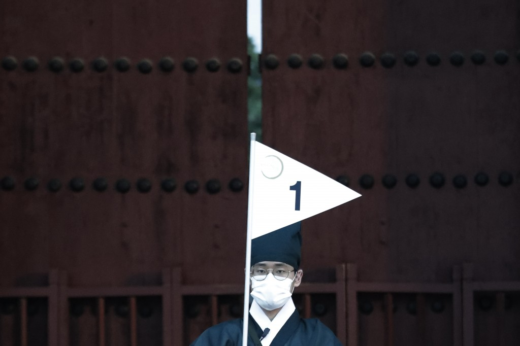 An employee wearing a face mask waits for arrival of visitors during the Moonlight Tour at Changdeokgung Palace in Seoul, South Korea, Thursday, Aug. ...