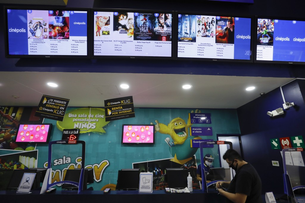 A moviegoer purchases tickets in the Cinepolis movie theater at Forum Buenavista mall, in Mexico City, Wednesday, Aug. 12, 2020. After being closed fo...