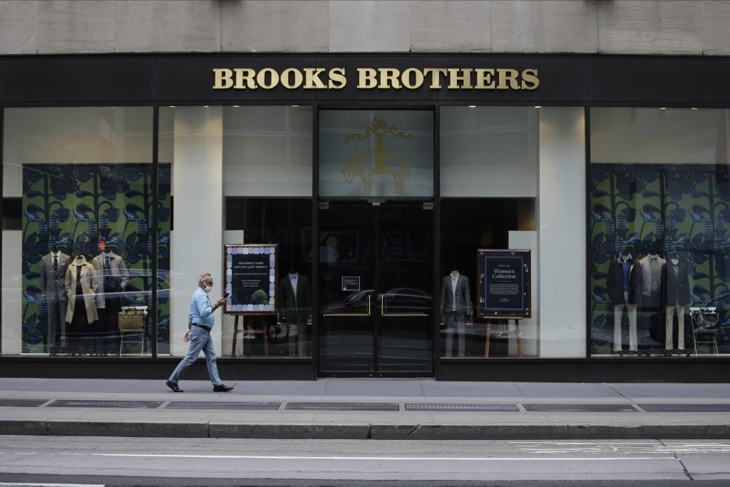 FILE - Pedestrians wearing protective masks walk past a Brooks Brothers location in a July 8, 2020 file photo, in New York. Brooks Brothers will be pu...