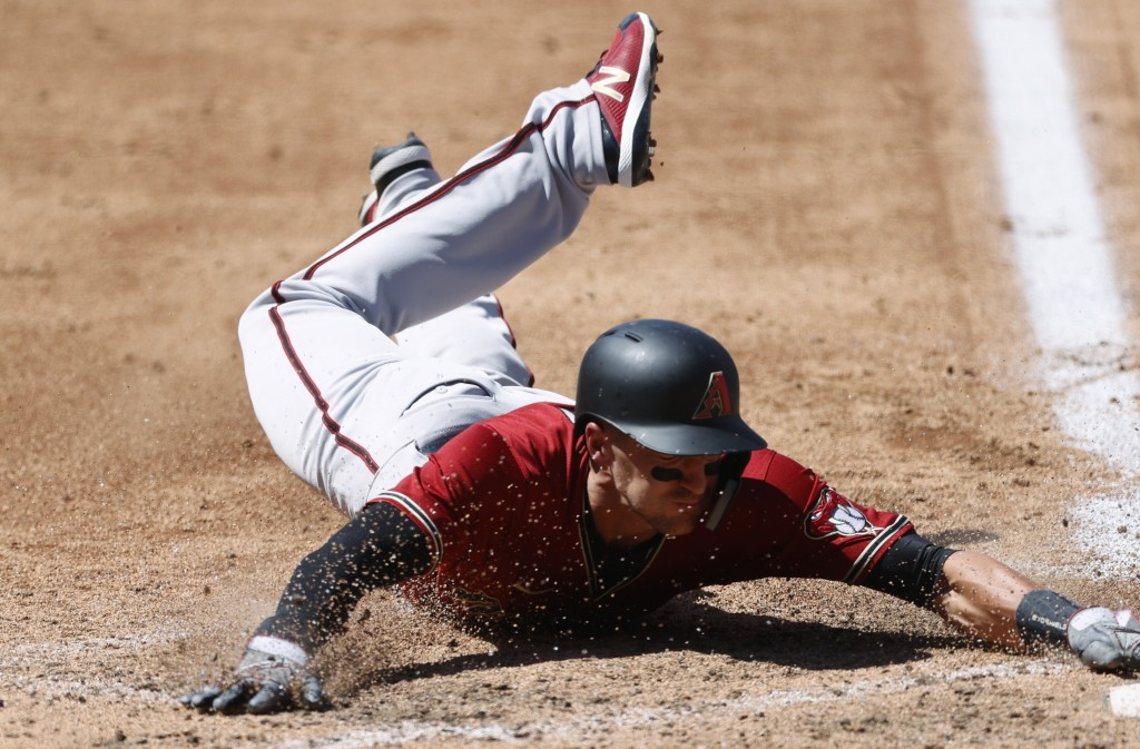 Arizona Diamondbacks' Nick Ahmed slides safely into home plate to score on a single hit by Ketel Marte off Colorado Rockies starting pitcher Antonio S...