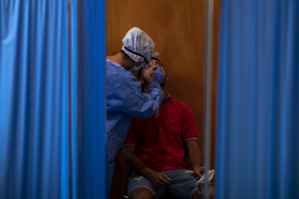 A Spanish NGO Open Arms volunteer takes a swab to test a man for COVID-19, at Vilafranca del Penedes in the Barcelona province, Spain, Tuesday, Aug. 1...