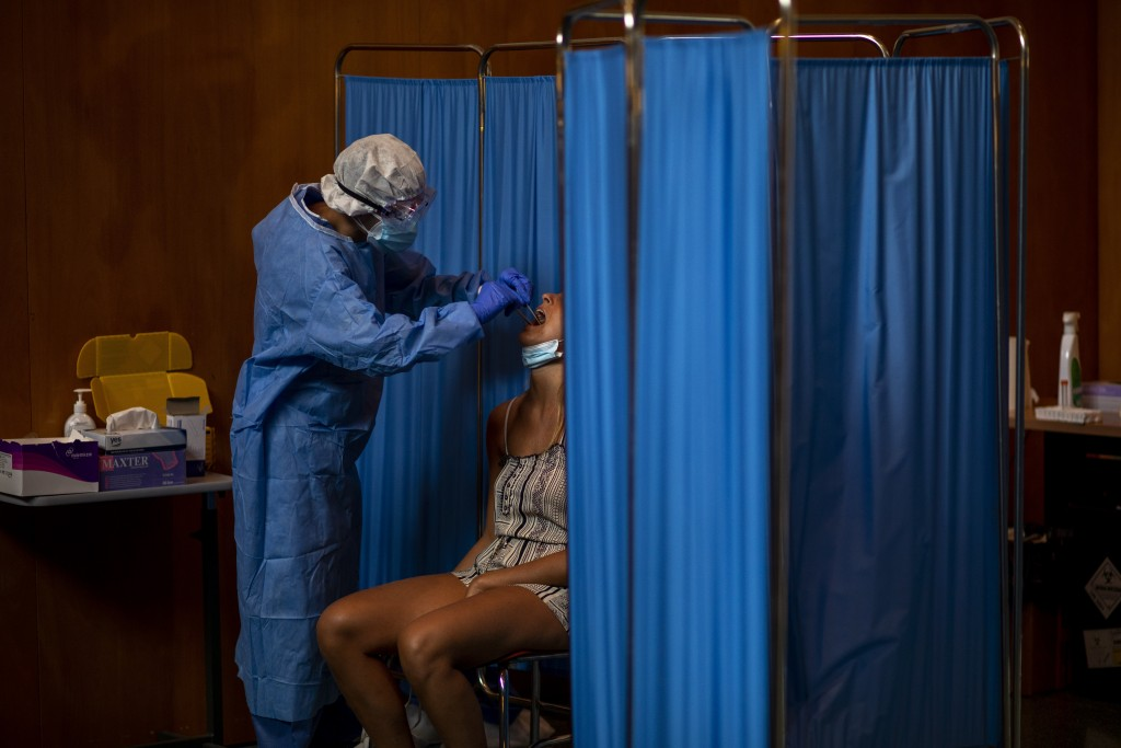 A Spanish NGO Open Arms volunteer takes a swab to test a woman for COVID-19, at Vilafranca del Penedes in the Barcelona province, Spain, Tuesday, Aug....
