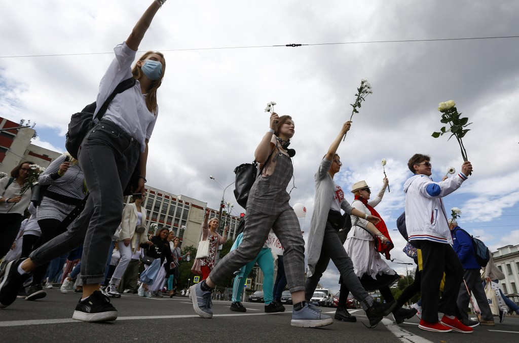 Belarusian women carry flowers on a rally in solidarity with protesters injured in the latest rallies against the results of the country's presidentia...