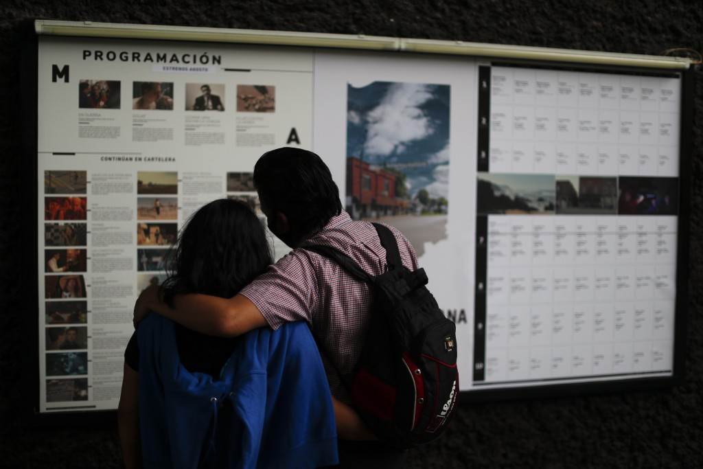 Filmgoers read listings for movies to be screened at the Cineteca Nacional, Mexico's film archive, in Mexico City, Wednesday, Aug. 12, 2020. After bei...