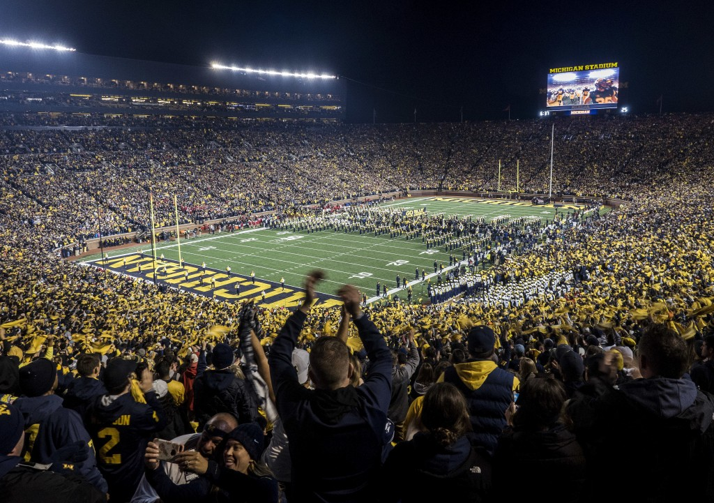 FILE - Fans cheer as the Michigan team takes the field at Michigan Stadium for an NCAA college football game against Wisconsin in Ann Arbor, Mich., Oc...