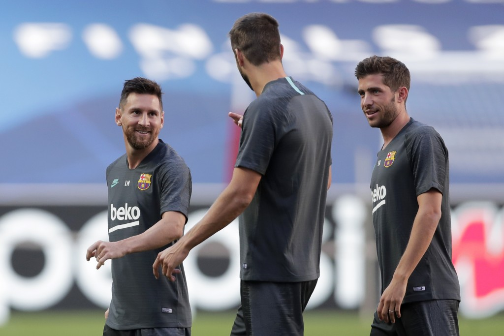 Barcelona players Lionel Messi, Gerard Pique and Sergi Roberto, from left to right, chat during a training session at the Luz stadium in Lisbon, Thurs...