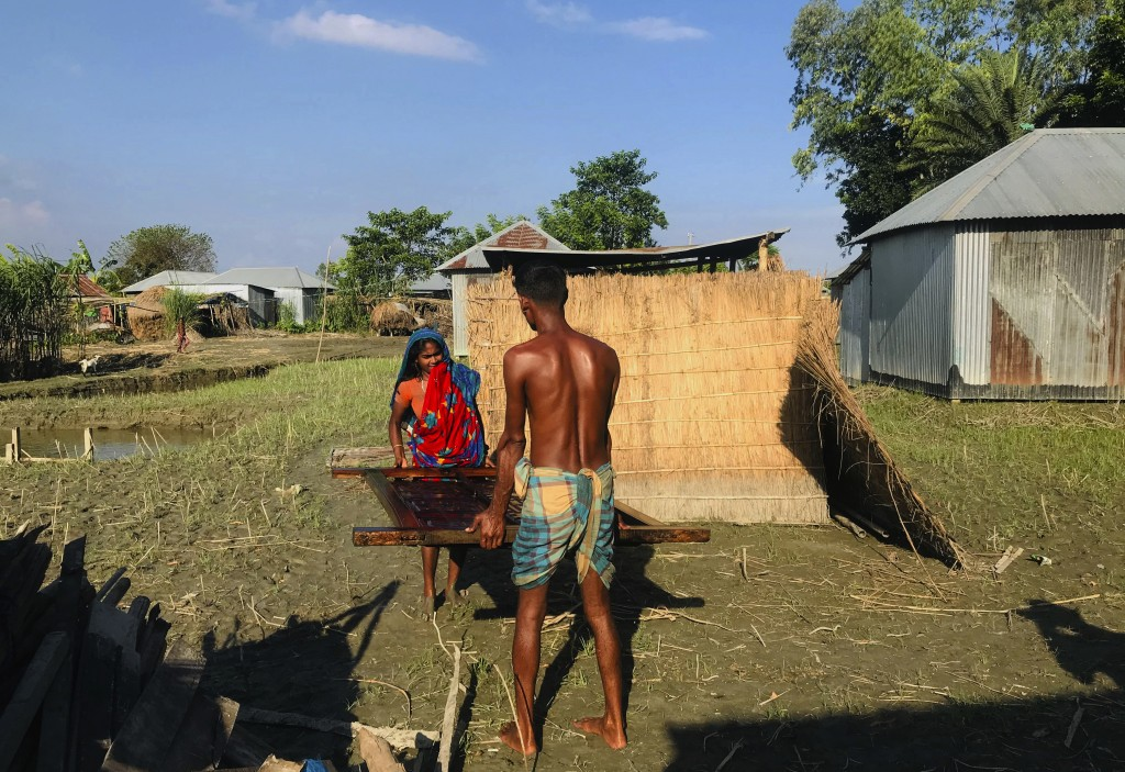 A Bangladeshi couple salvages a wooden window of their house after the flood water inundated their village in Manikganj, some 100 kilometers (62 miles...