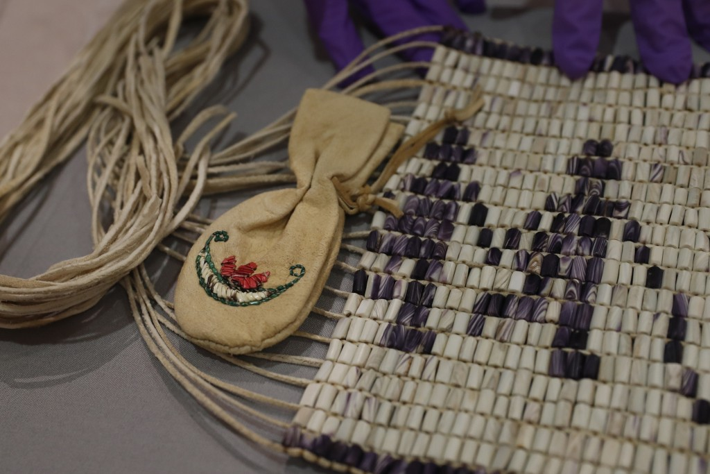Co-curator Jo Loosemore examines a recently created wampum belt made by members of the Wampanoag Native America people, after its unpacking and prior ...