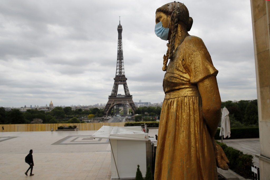 FILE- In this file photo dated Monday, May 4, 2020, a statue wears a mask along Trocadero square close to the Eiffel Tower in Paris. Britain will requ...