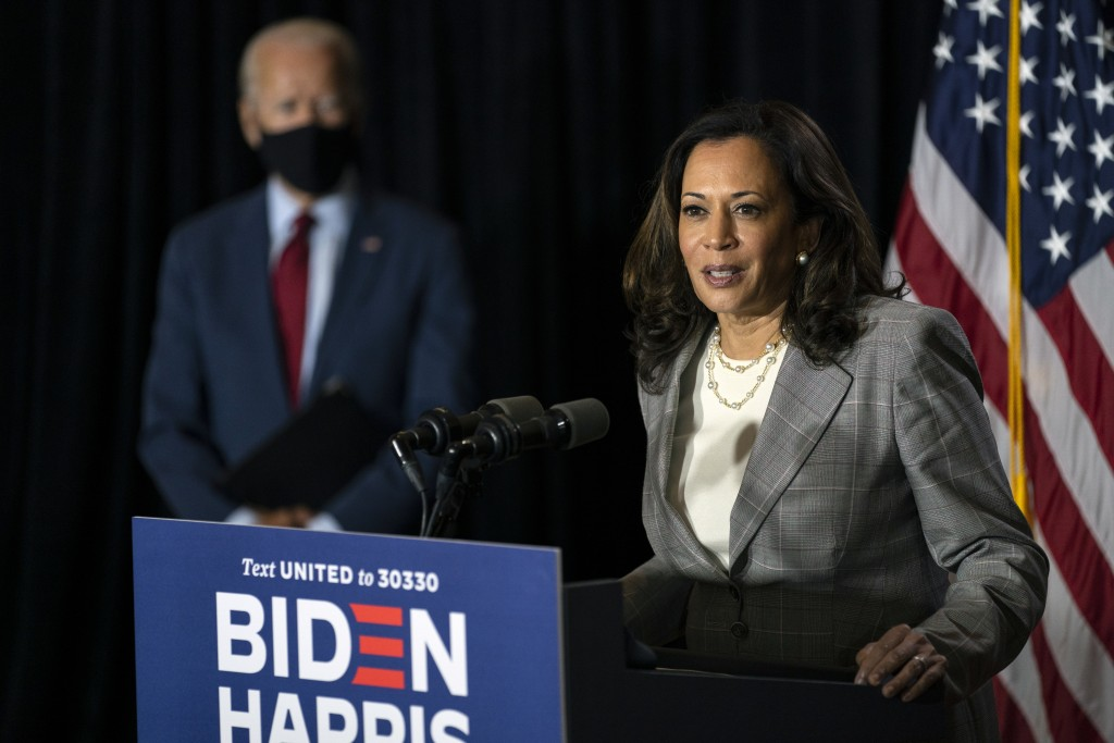 Democratic presidential candidate former Vice President Joe Biden stands left as his running mate Sen. Kamala Harris, D-Calif., speaks at the Hotel Du...