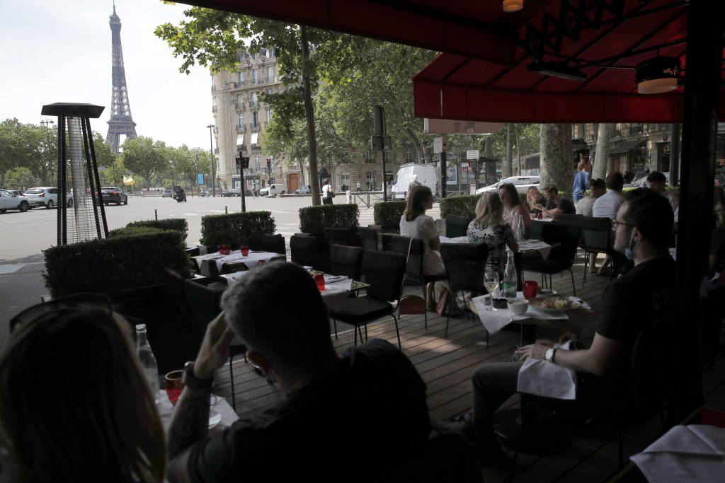 FILE - In this Wednesday, June 3, 2020 file photo people enjoy a lunch on a terrace of the restaurant Chez Francis, in Paris. Britain will require all...