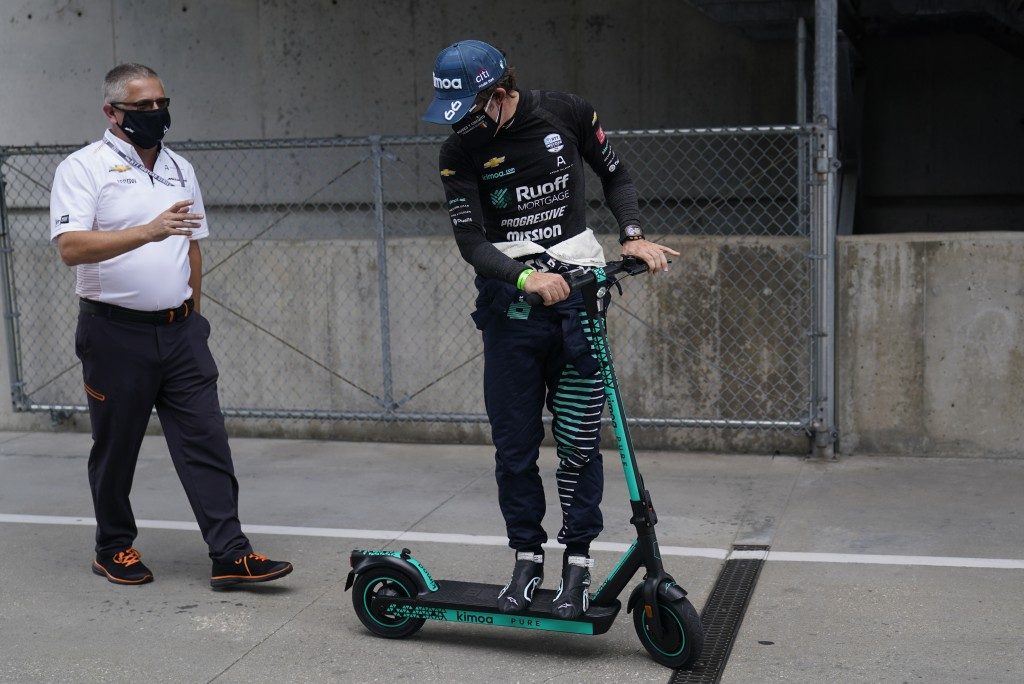 Gil de Ferran, left, talks with Fernando Alonso, of Spain, as the go back to the garage during a practice session for the Indianapolis 500 auto race a...
