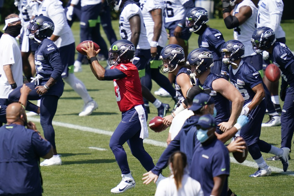 Seattle Seahawks quarterback Russell Wilson (3) reaches for a ball as he runs through a drill with teammates Thursday, Aug. 13, 2020, in a practice du...