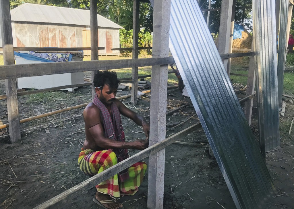A Bangladeshi man builds a shelter for his family after the flood water inundated his village in Manikganj, some 100 kilometers (62 miles) from Dhaka,...