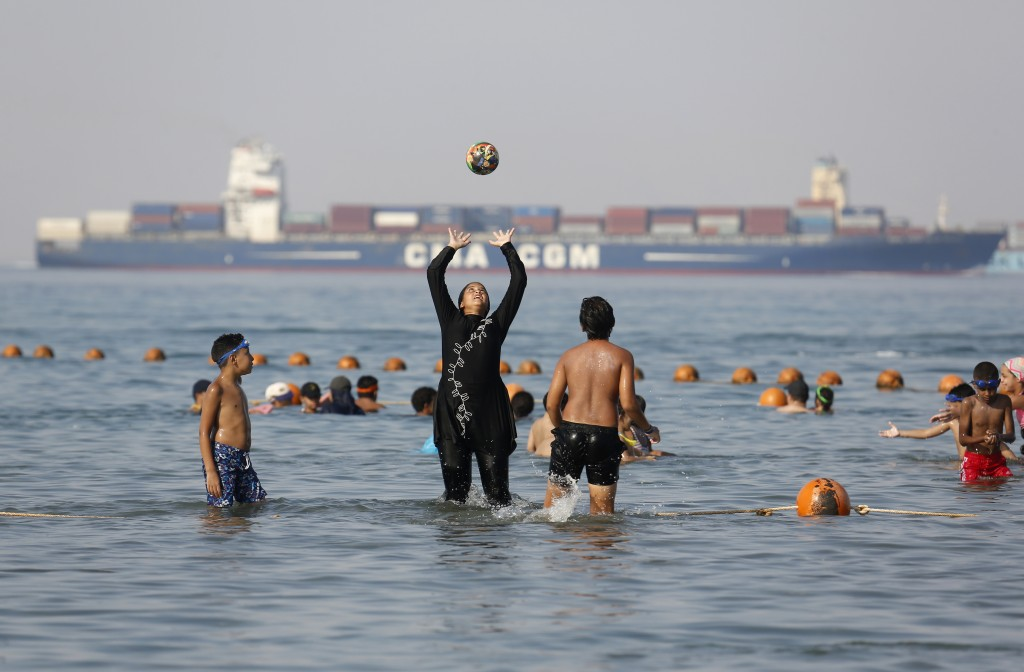 FILE - In this July 19, 2018 file photo, holidaymakers play in the Red Sea, at El Sokhna beach in Suez, Egypt, Egypt. The burkini, a swimsuit worn by ...