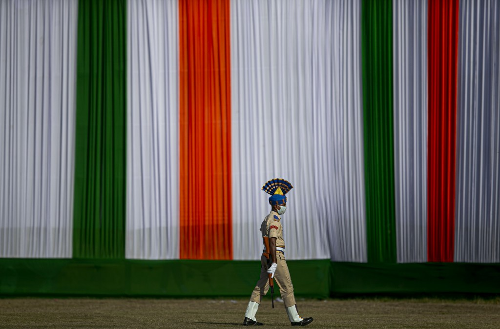 An Indian paramilitary soldier wearing a face mask walks to join his group to participate in the final dress rehearsals for India's Independence Day c...
