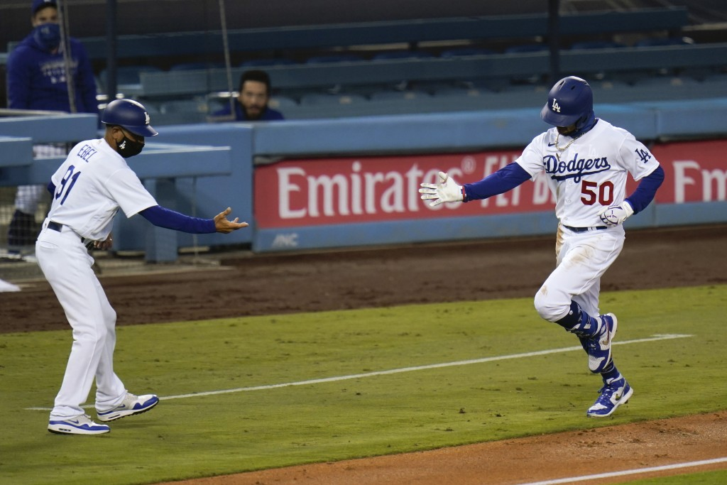 Los Angeles Dodgers' Mookie Betts, right, keeps distance as he celebrates his second home run of a baseball game with third base coach Dino Ebel durin...