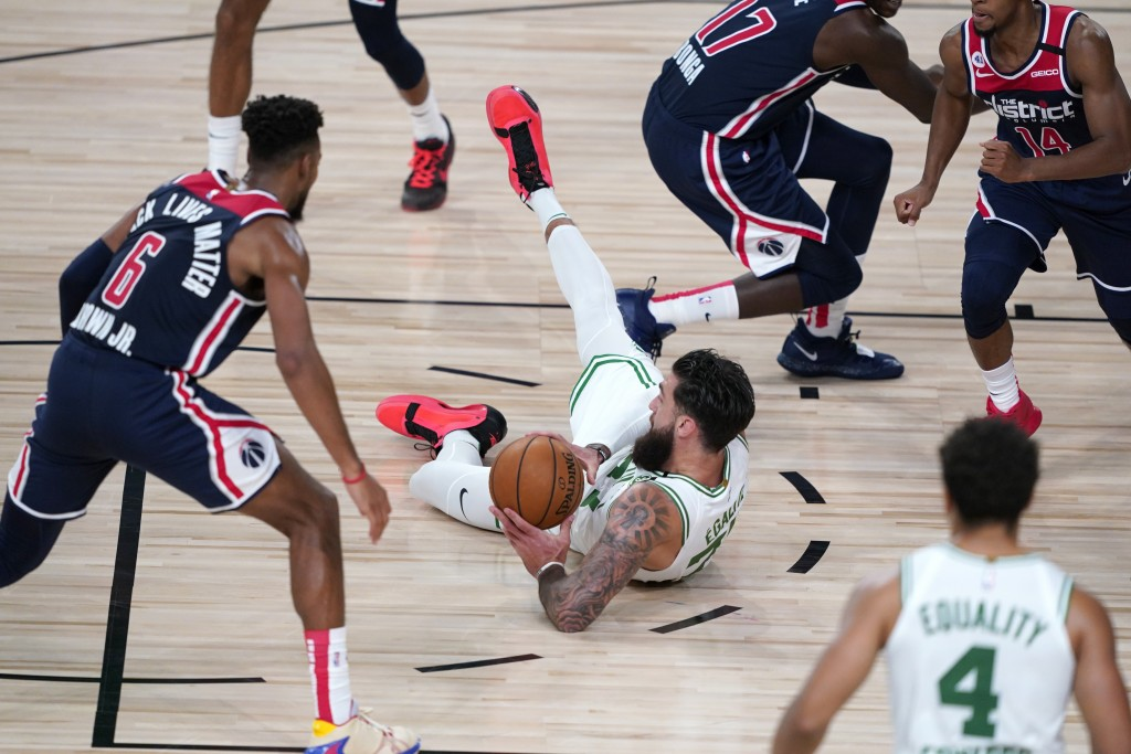 Boston Celtics' Vincent Poirier tries to pass while falling during the second half of an NBA basketball game against the Washington Wizards Thursday, ...