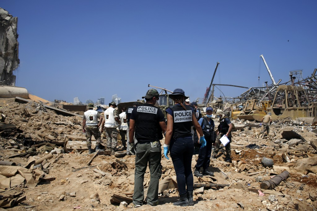FILE - In this Aug. 8, 2020 file photo, French criminal police officers work on the site of this week's massive explosion in the port of Beirut, Leban...