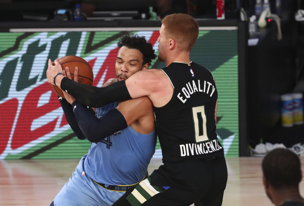 Milwaukee Bucks guard Donte DiVincenzo (0) defends against Memphis Grizzlies guard Dillon Brooks (24) in the first half of an NBA basketball game Thur...