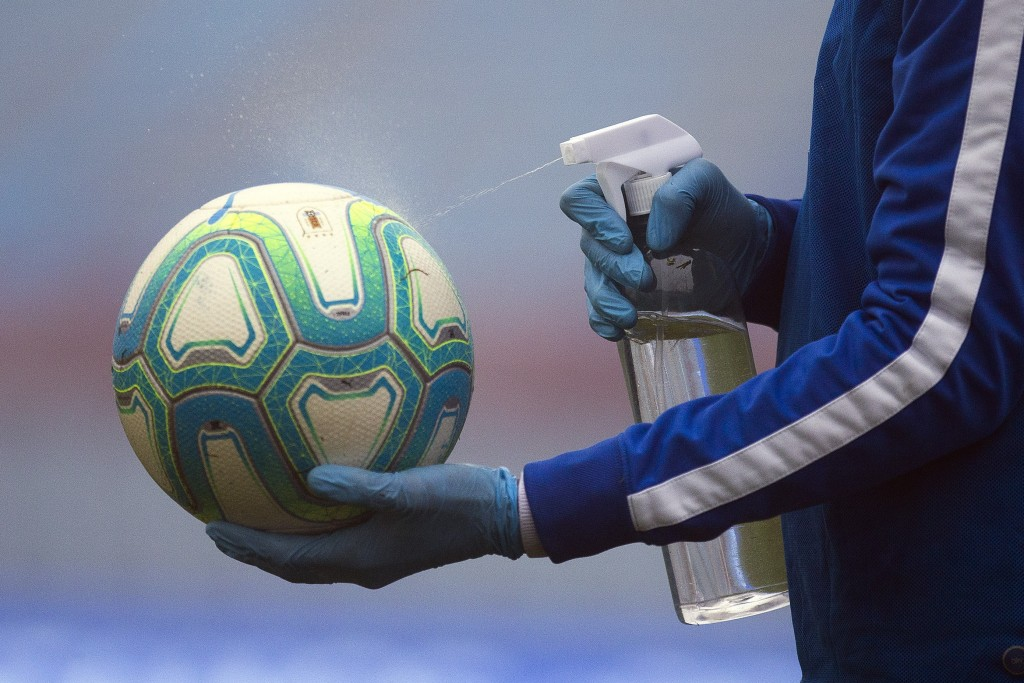 A ball catcher wearing plastic gloves amid the new coronavirus pandemic, disinfects the ball during a local championship soccer match between Nacional...