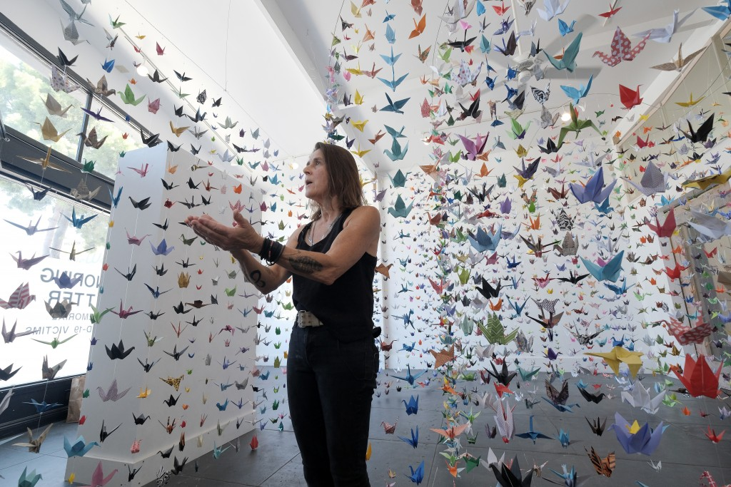 Artist Karla Funderburk, owner of Matter Studio Gallery, talks about the thousands of origami paper cranes hanging in an exhibit honoring the victims ...