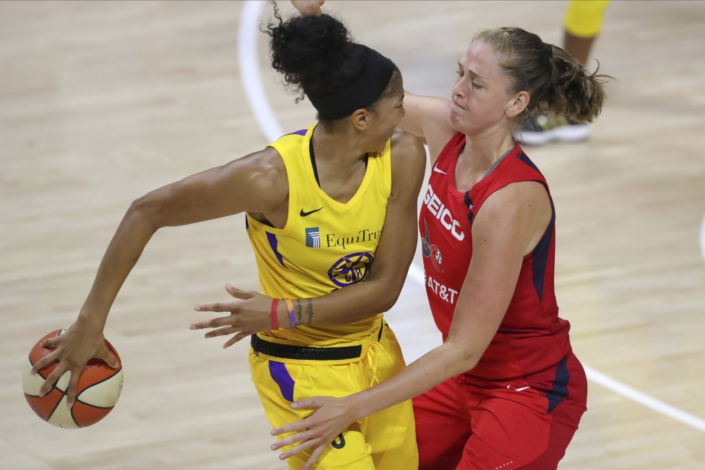 Los Angeles Sparks' Candace Parker, left, passes behind her back as she is defended by Washington Mystics' Emma Meesseman during the first half of a W...