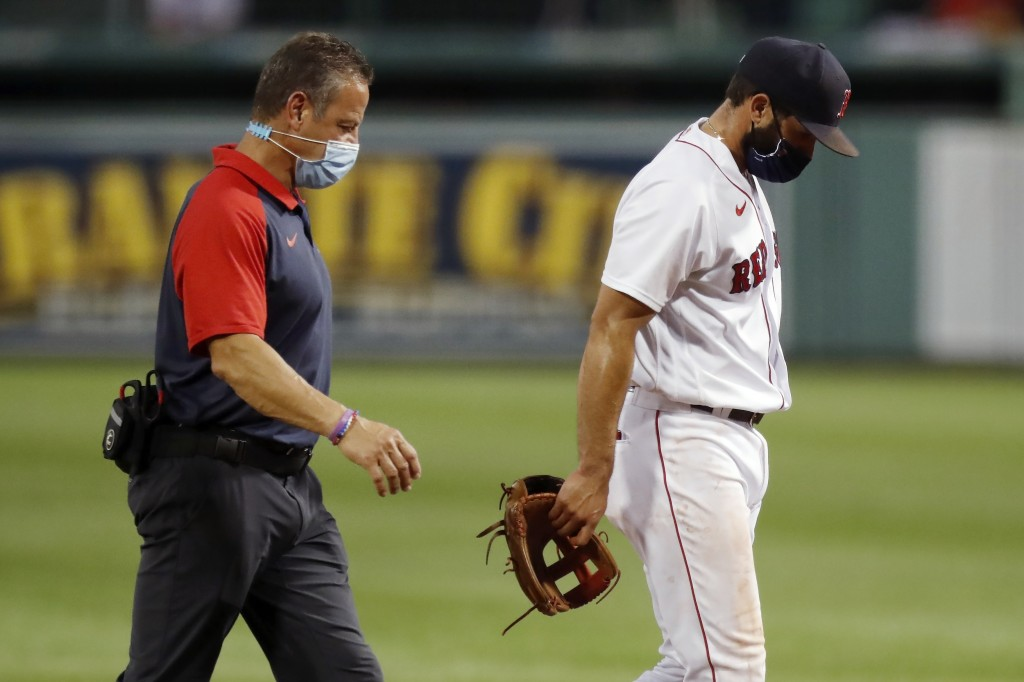 Boston Red Sox infielder Jose Peraza, right, leaves the field with a trainer after being injured while pitching during the ninth inning of a baseball ...