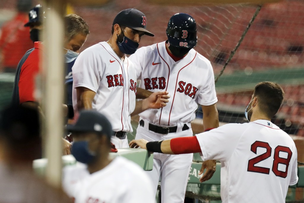 Boston Red Sox infielder Jose Peraza, center left, enters the dug out after being injured while pitching during the ninth inning of a baseball game ag...