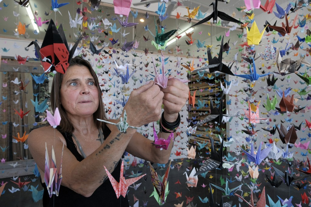 Artist Karla Funderburk, owner of Matter Studio Gallery, adjusts one of of the thousands of origami cranes hanging during an exhibit honoring the vict...