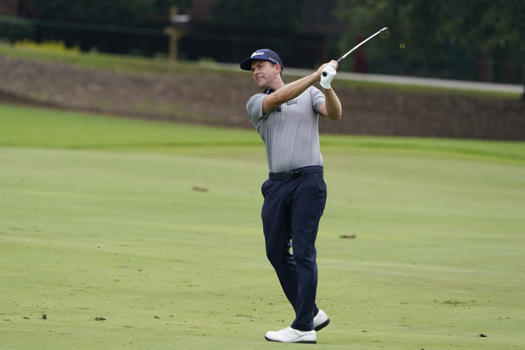 Webb Simpson hits from the fairway on the eighth hole during the first round of the Wyndham Championship golf tournament at Sedgefield Country Club on...