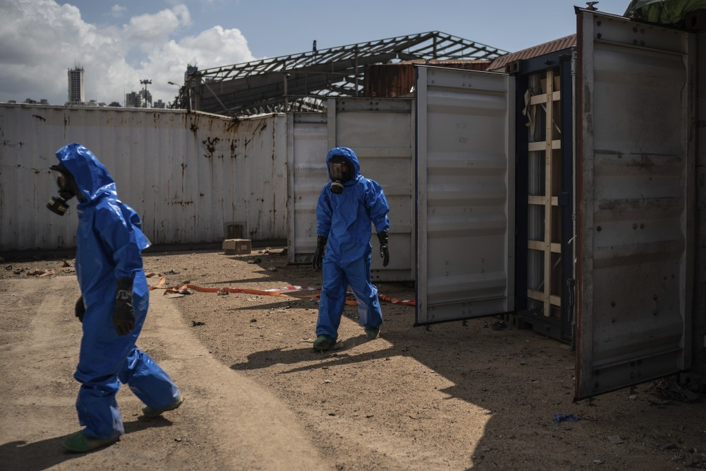 FILE - In this Aug. 10, 2020 file photo, French emergency workers, part of a special unit working with chemicals, walk next to damaged containers near...