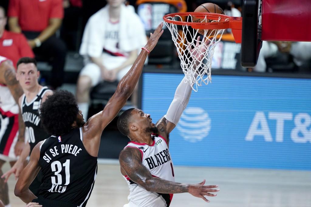 Portland Trail Blazers' Damian Lillard, right, goes up for a shot against Brooklyn Nets' Jarrett Allen (31) during the first half of an NBA basketball...